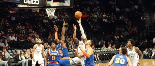 Nets guard D'Angelo Russel going up for a shot over Knicks guard Tim Hardaway Jr.