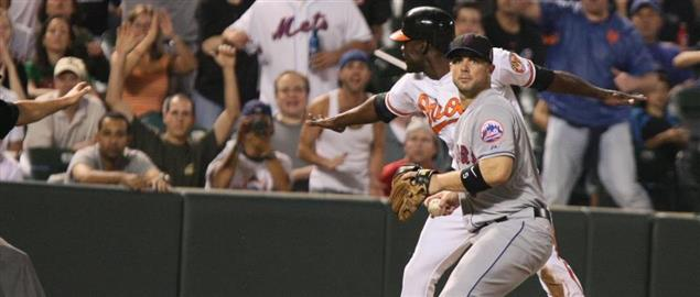 Orioles' Pie signals safe at third while Mets Wright surveys field in 9th inning, 6/18/09.